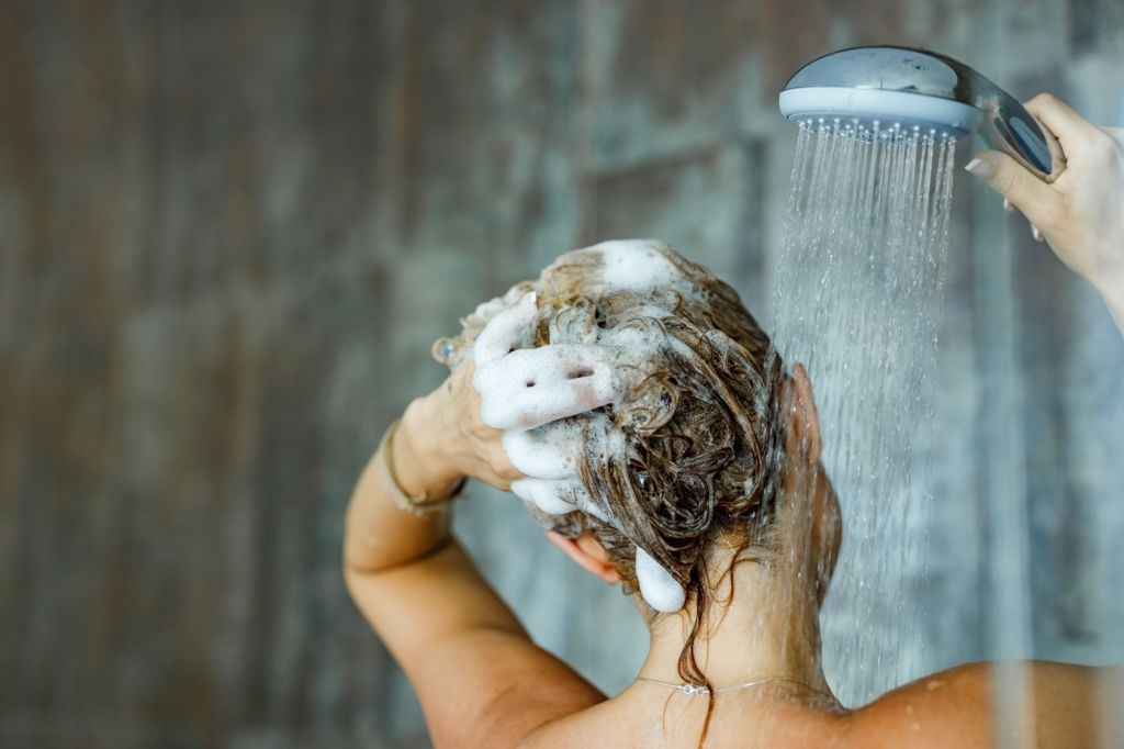 Back view of a woman washing her hair with a shampoo in bathroom.