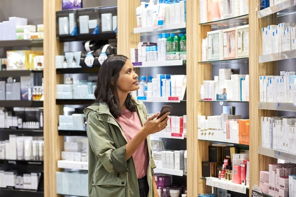 Female customer searching medicine on shelf from rack at pharmacy. Young woman is holding smart phone. She is wearing jacket at medical store.