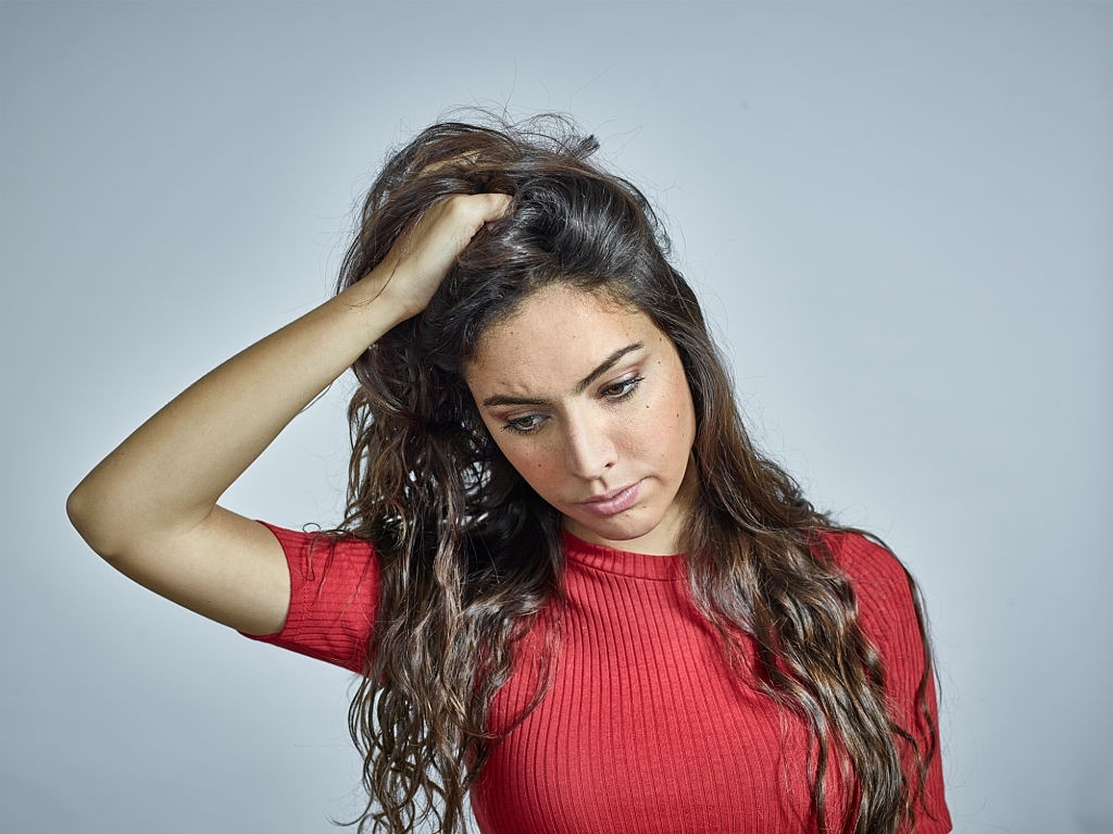 Portrait of young brunette female wearing red dress, looking down and holding her long hair.