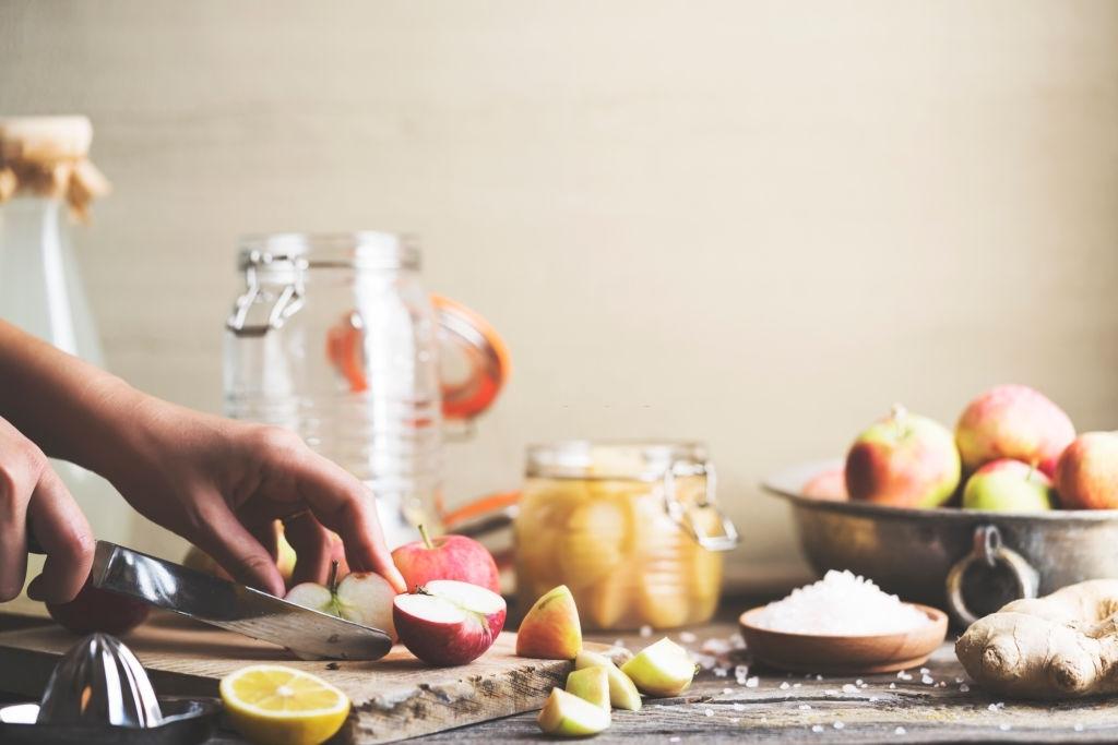 Making homemade apple cider vinegar, preparation process. Hand cutting apples.